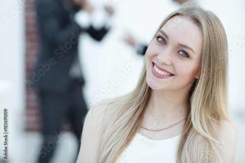 close-up portrait of a young woman against the background of colleagues