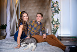 Beautiful young couple in the New Year atmosphere with puppies of the Husky - 183691263