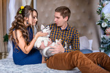 Beautiful young couple in the New Year atmosphere with puppies of the Husky - 183691291