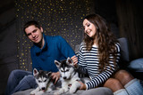 Beautiful young couple in the New Year atmosphere with puppies of the Husky - 183691805