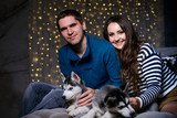 Beautiful young couple in the New Year atmosphere with puppies of the Husky - 183691823