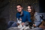 Beautiful young couple in the New Year atmosphere with puppies of the Husky - 183691843