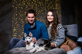Beautiful young couple in the New Year atmosphere with puppies of the Husky - 183691859