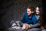 Beautiful young couple in the New Year atmosphere with puppies of the Husky - 183691877