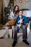 Beautiful young couple in the New Year atmosphere with puppies of the Husky - 183692042