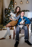 Beautiful young couple in the New Year atmosphere with puppies of the Husky - 183692061
