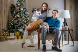 Beautiful young couple in the New Year atmosphere with puppies of the Husky - 183692245
