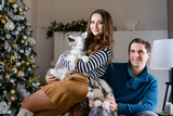 Beautiful young couple in the New Year atmosphere with puppies of the Husky - 183692254