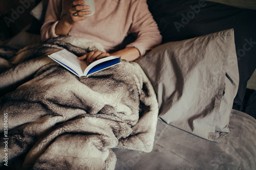 Woman on bed reading book and drinking coffee Poster