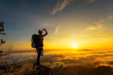 A backpacker girl travels on the mountains ahead as the sea fog and sunrise. - 183700820