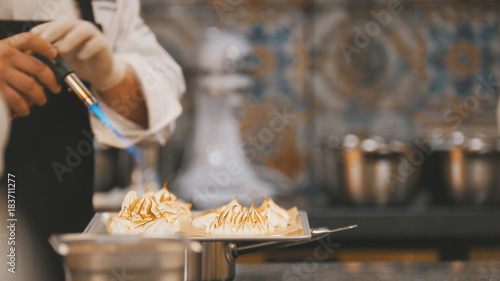Cooking of meringue - chef use fire for decorates dessert
