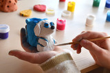 Making toys, paints a pottery clay dog figure with gouache. Indoors creative leisure for children. Supporting creativity, learning by doing, DIY project, hand craft. Master class of art. - 183718667