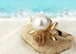 Macro of Jewelery ring with pearl on sand beach