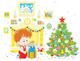Little boy with his holiday gift near a fireplace and a colorfully decorated Christmas tree - 183720657