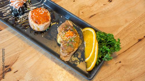 Plexiglas Sushi bar Fresh salmon eggs sushi on a black plate (Japanese food).