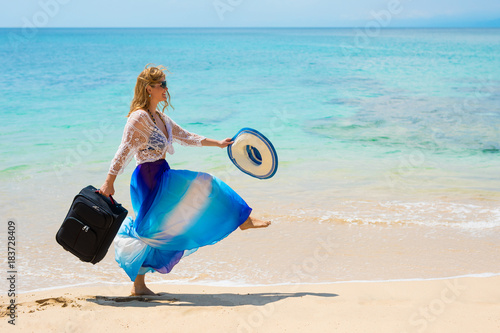 Happy woman walking on the beach with suitcase in hand
