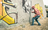 Fototapeta Młodzieżowe - Street artist painting colorful graffiti on generic wall - Modern art concept with urban guy performing and preparing live murales with multi color aerosol spray - Contrast retro vintage filter © Mirko