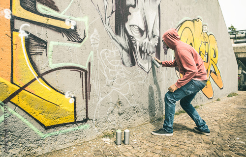 Street artist painting colorful graffiti on generic wall - Modern art concept with urban guy performing and preparing live murales with multi color aerosol spray - Contrast retro vintage filter - 183733232