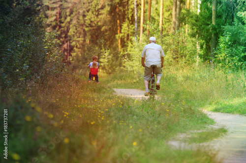 Poster active senior with grandkids riding bikes in nature