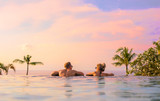 Romantic couple looking at beautiful sunset in luxury infinity pool - 183749497