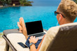 Man chilling by the pool and using laptop computer