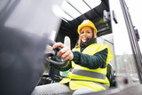 Woman forklift truck driver in an industrial area. - 183764225