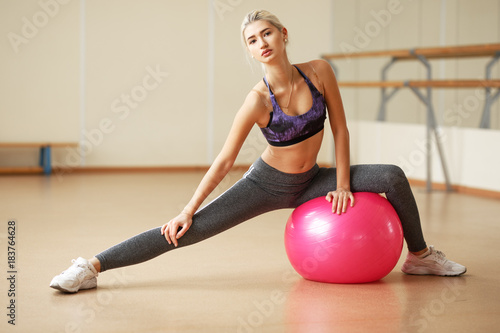 Attractive slim blonde female doing stretching exercises on blue mat in modern bright fitness center.