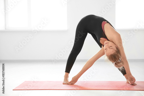 Young woman practicing yoga in light room