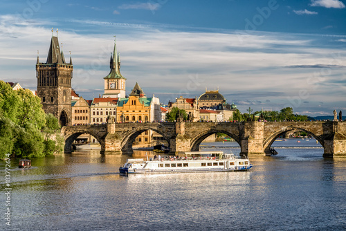 Charles bridge and cruiseship on river Vltava, Prague - Czech republic Poster