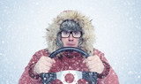 Man in winter clothes with a steering wheel, snow, blizzard. Concept car driver