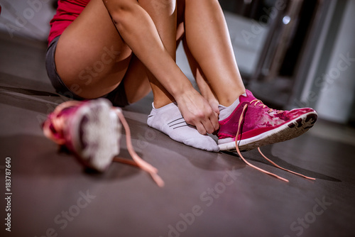Póster Close up of young fitness girl sitting on the gym floor and putting on her pink sneakers