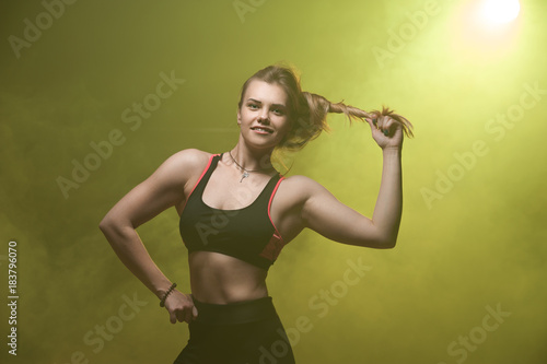 Poster Portrait of happy smiling fitness woman wearing sportswear posing against yellow smoky background.