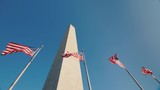 Low angle shot Washington monument in DC, USA, American flags flap below - 183824450