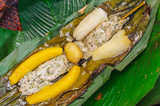 Above view of delicious typical amazonia food, fish cooked in a leaf with yucca and plantain, served in a wooden plate over a wooden table - 183832661