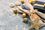 Holiday place setting with napkin, fork and knife tied with a gold ribbon - 183838422