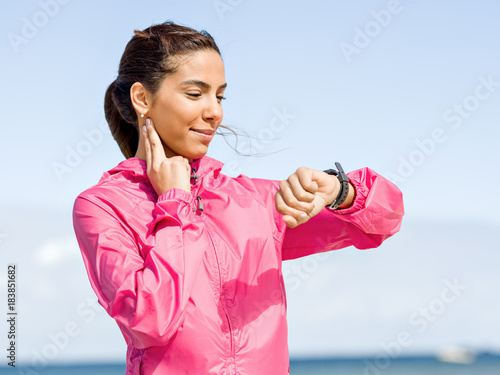 Staande foto Jogging Young woman on beach checking heart rate after run