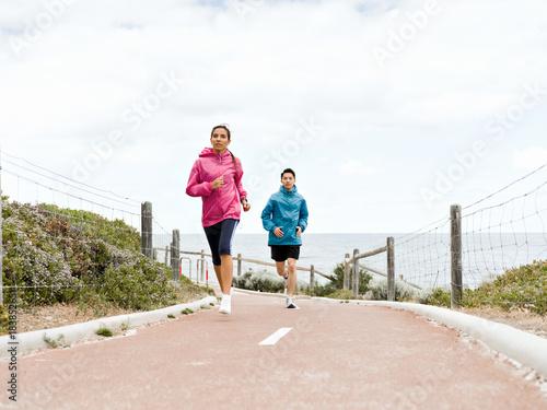 Plexiglas Fitness Young Couple Running along sea shore