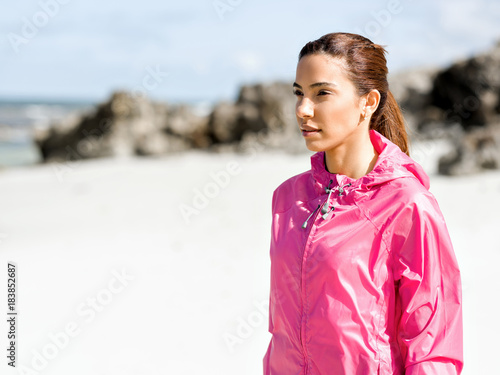 Sticker Athletic woman in sportswear standing at the seaside