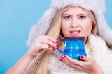 Blonde woman in winter furry hat drinking - 183873485