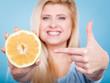 Woman pointing on grapefruit citrus fruit