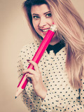 Happy woman holding big oversized pencil - 183876426
