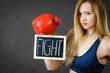 Woman wearing boxing glove holding fight sign
