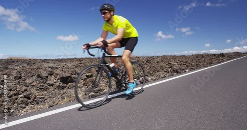 Professional cyclist riding racing bike in race competition on open road. Sports athlete man biking with high intensity on highway during summer cardio workout training. SLOW MOTION, RED EPIC.