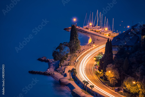 Fotobehang Nachtblauw Torbole,Lago di Garda ,Italy - 07 JULY 2014:Panorama of Torbole and Garda lake by night , a small town on Lake Garda, Italy. Europa