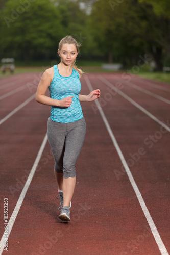 Deurstickers Jogging Junge Frau auf der Aschebahn