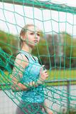 Fußballerin posiert im Netz von einem Tor - 183923820