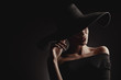 Quadro Dramatic dark studio portrait of elegant woman in black wide hat and black dress. Hidden eyes.