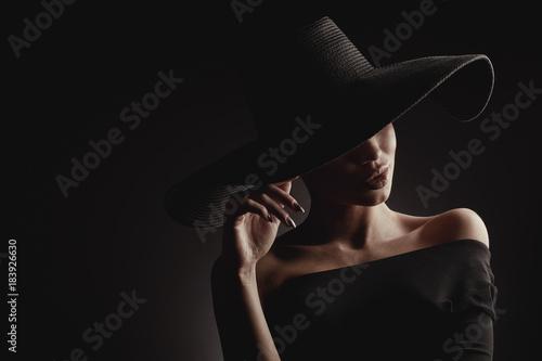 Dramatyczny ciemny pracowniany portret elegancka kobieta w czarnym szerokim kapeluszu i czerni sukni. Ukryte oczy.