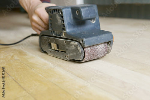 Hand held belt sander. Sanding birch parquet by hand. - 183932661