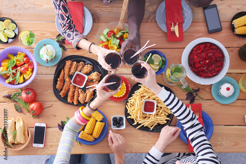 Top view of group of people having dinner together while sitting at wooden table. Food on the table. People eat fast food. - 183932897